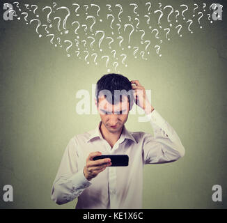 Portrait jeune homme confus en regardant son téléphone intelligent a de nombreuses questions isolé sur fond de mur Banque D'Images