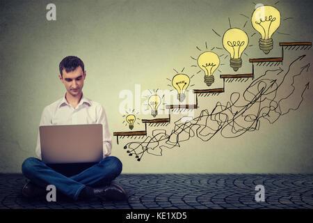 Heureux jeune homme entrepreneur travaillant sur ordinateur assis sur un étage dans son bureau réussi à augmenter Banque D'Images