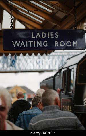 Un panneau suspendu à une plate-forme à une station de train qui lit, 'chers salle d'attente', uk