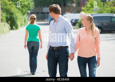 Jeune femme criant à son petit ami à la recherche à une autre femme dans la rue Banque D'Images
