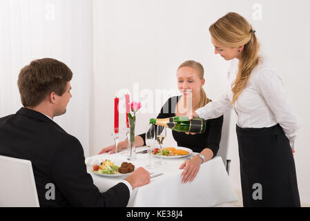 Female waitress pouring champagne en verre pour happy young couple in restaurant Banque D'Images