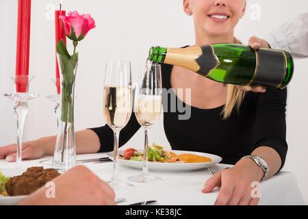 Photo gros plan de female waitress pouring champagne en verre pour happy young couple in restaurant Banque D'Images