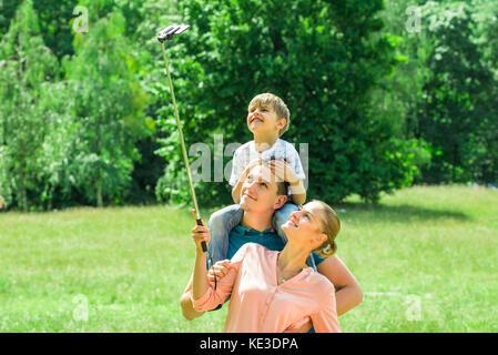 Smiling young family prenant en selfies park Banque D'Images