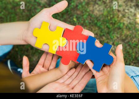 Close-up of hands holding trois pièces de puzzle colorées Banque D'Images