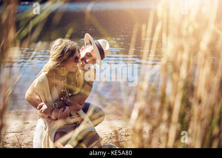 Young couple hugging at sunny summer riverside Banque D'Images
