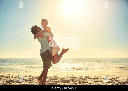 Copain copine ludique de levage sur la plage de l'océan l'été ensoleillé Banque D'Images