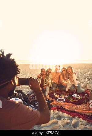 Jeune homme au téléphone appareil photo photographier friends enjoying pique-nique sur la plage d'été ensoleillé Banque D'Images