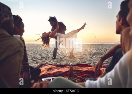 Young couple dancing ludique sur sunny summer beach Banque D'Images