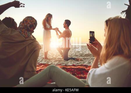 Jeune homme propose à la femme sur la plage avec des amis de l'été ensoleillé Banque D'Images