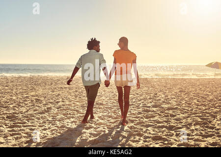 Young couple holding hands, walking on sunny summer beach Banque D'Images