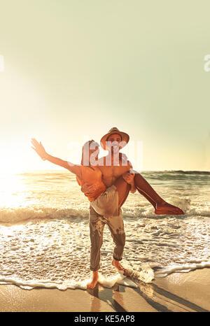 Portrait amusant jeune couple sur la plage ensoleillée d'été de l'océan