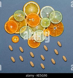 Aliments santé et médecine concept. comprimés de vitamine C et d'agrumes dans la forme de nuages et de pluie. agrumes Banque D'Images