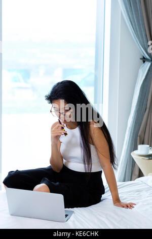 Young Asian business woman travaillant dans sa chambre d'hôtel Banque D'Images