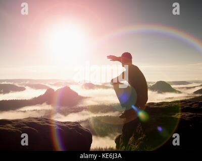 Flare. solide, défaut de l'objectif de réflexion. l'homme dans les vêtements de sport est assis sur le bord de la falaise et à la vallée de Misty ci-dessous. paysage d'automne mont brumeux.