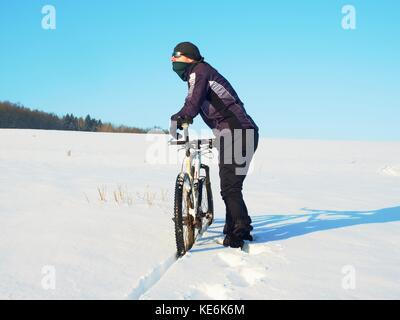 Biker poussant VTT sur neige gel. d'hiver ensoleillée. météo biker vélo pousse dans la neige profonde en prairie. incroyable journée ensoleillée. petit snow fl