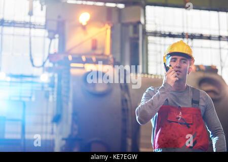 Un travailleur de sexe masculin parle de talkie-walkie dans une usine d'acier Banque D'Images