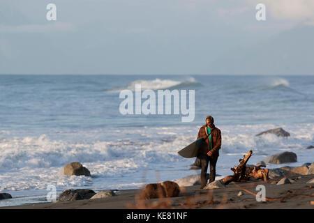 Marcher avec un surf surfer le long de la côte près de Yakutat, sud-est de l'Alaska, USA Banque D'Images
