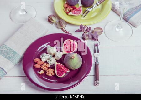Service de la table, figues fraîches, fruits, baies, noix, fromage blanc sur un fond de bois Banque D'Images