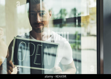 Waiter holding chalkboard with open word