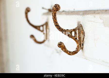 Vieux rouillé cintre avec crochets à l'abandonné accueil Banque D'Images