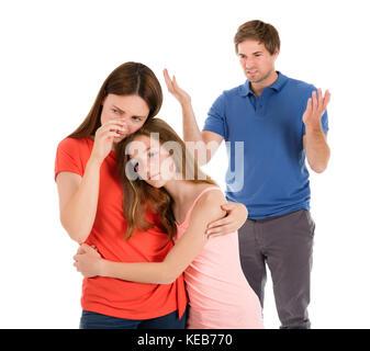 Fille mère consolatrice pendant que son parent ayant un conflit isolé sur fond blanc Banque D'Images