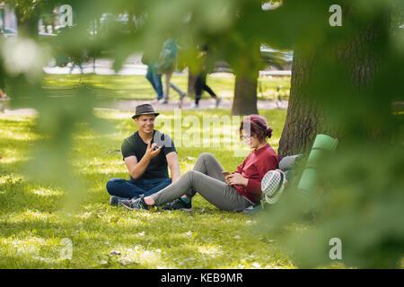 Jeune homme et femme les touristes avec des sacs à dos ont reste dans le parc Banque D'Images
