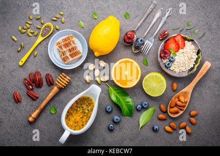 Ingrédients pour les aliments santé contexte noix mélangées, baies, fruits, miel, myrtille, orange, amandes, d'avoine Banque D'Images