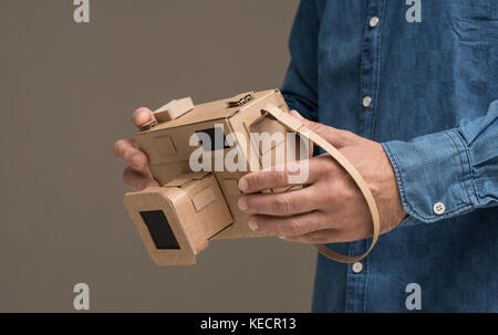 La tenue d'un photographe respectueux de la main de l'appareil photo en carton, de l'artisanat et la créativité Banque D'Images