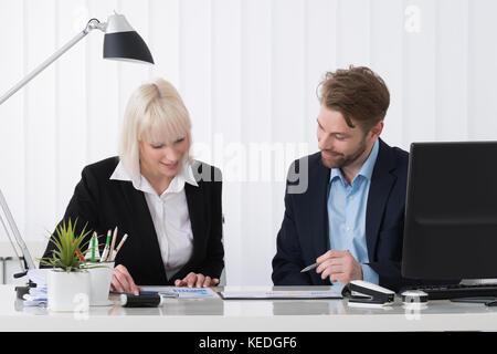 Deux hommes d'affaires l'analyse graphique dans l'office de tourisme Banque D'Images