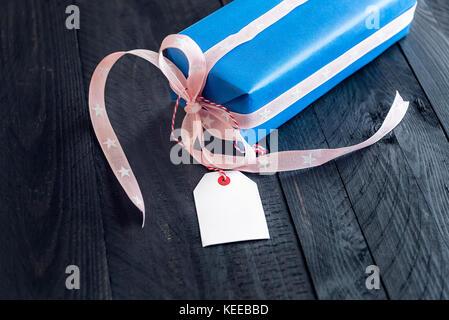 Present, enveloppé dans du papier bleu et attachés à un ruban rose, et Bow, avec une étiquette vide attaché à lui, Banque D'Images