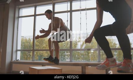 Jolie jeune fille jeune homme musclé et instructeur de conditionnement physique faisant fort aller exercer pendant Banque D'Images