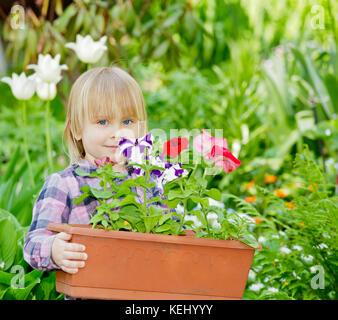 Little girl holding container avec des fleurs Banque D'Images
