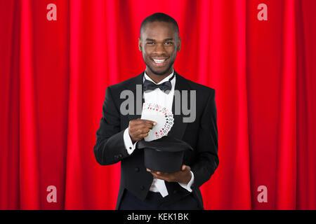 Les jeunes professionnels magicien montrant tour avec des cartes à jouer