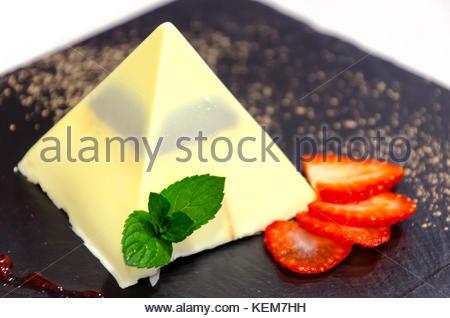 Pyramide au chocolat blanc dans une plaque noire avec les tranches de fraises Banque D'Images