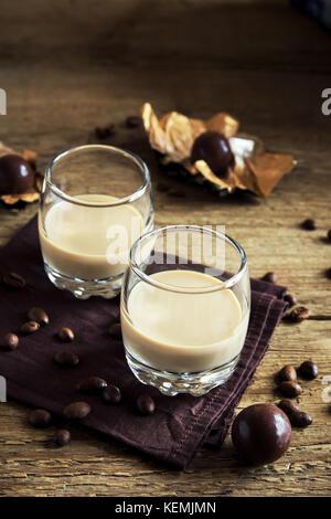 Irish Cream Liqueur de café avec de la glace, bonbons au chocolat et les grains de café sur fond de bois rustique - maison de l'alcool boire festif