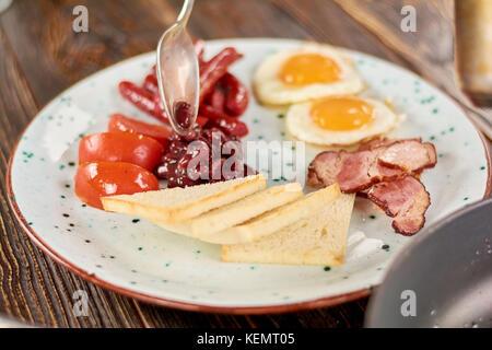 Le petit déjeuner anglais complet sur la plaque. chef putting haricots sur plaque avec petit déjeuner anglais. Petit Banque D'Images