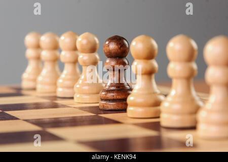 Un pion noir se dresse au milieu d'une rangée de pions blancs, l'autre soulignant ses différentes caractéristiques de l'acceptation du groupe.