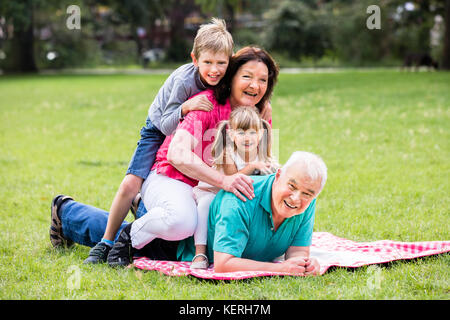 Happy Family having fun lying on grass in park Banque D'Images
