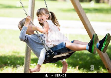 Heureux les jeunes enfants - garçon et fille jouissant sur la balançoire dans le parc Banque D'Images