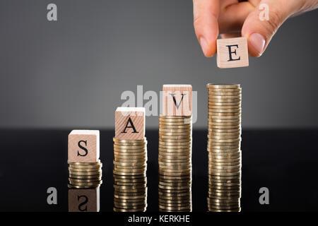 Personne mains mettre Enregistrer mot lettres sur pile de pièces sur fond gris Banque D'Images