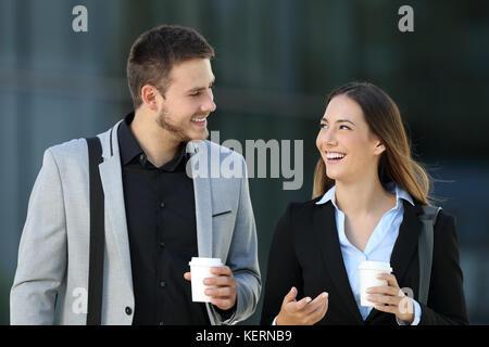 Heureux couple de cadres de marcher vers la caméra et la conversation sur la rue avec un immeuble de bureaux à l'arrière Banque D'Images