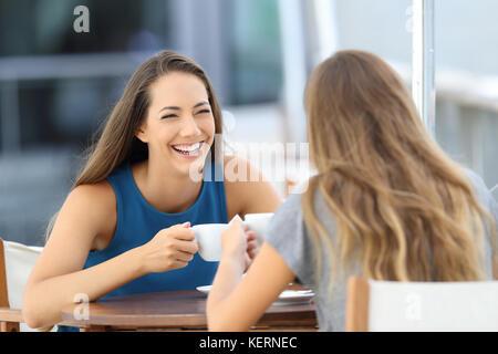Deux amis heureux parler et rire assis sur une terrasse de restaurant Banque D'Images