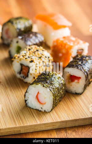 Rouleaux de sushi japonais sur planche à découper en bois. Banque D'Images