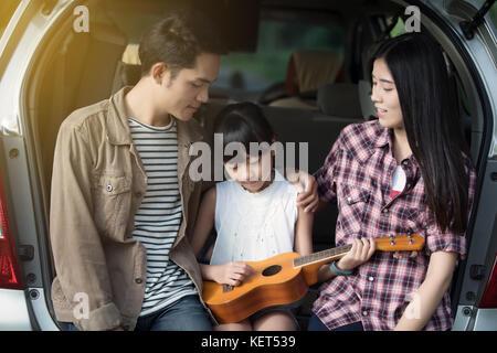 Happy little girl playing ukulele avec asian family dans la voiture pour profiter de la route et les vacances d'été Banque D'Images