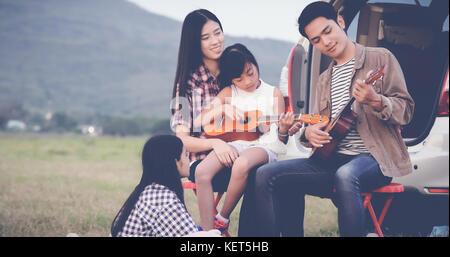 Happy little girl playing ukulele avec asian family dans la voiture pour profiter de la route et les vacances d'été,soft Banque D'Images