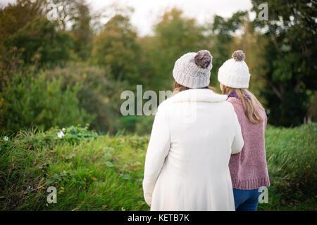 Deux jeunes filles / sœurs marcher à travers champs en automne Banque D'Images