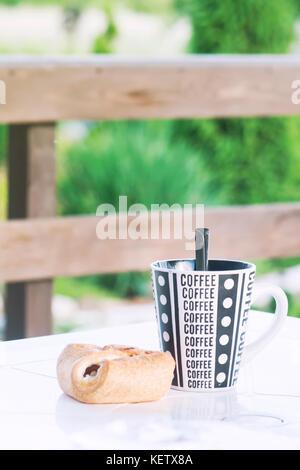 Une tasse de café avec un croissant sur la table, une véranda d'une maison de campagne, une photo aux tons Banque D'Images