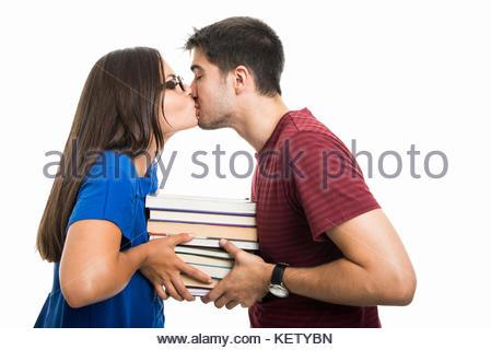 De jeunes étudiants holding pile of books et les baisers isolé sur fond blanc Banque D'Images