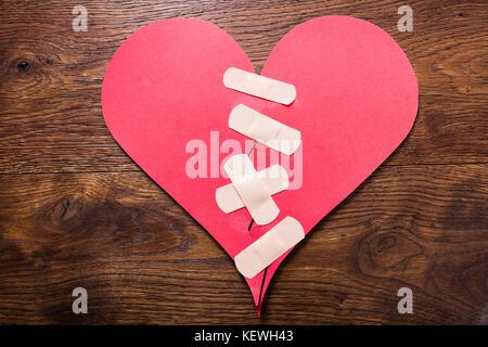 High angle view of a broken heart fixe avec bandage sur un bureau en bois Banque D'Images