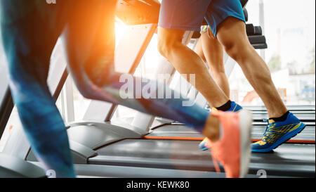Photo de personnes fonctionnant sur tapis roulant dans une salle de sport Banque D'Images